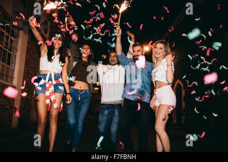 Groupe de jeunes ayant une partie, à l'extérieur. Les jeunes hommes et femmes multiraciales célébrant de confettis. Banque D'Images