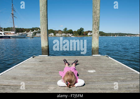 Little girl lying on dock with hands behind head Banque D'Images