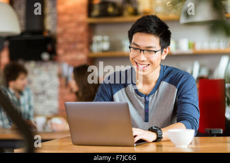 Happy cheerful young asian male dans les verres smiling and using laptop in cafe Banque D'Images