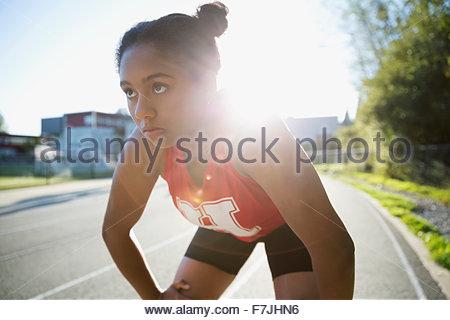 Les mains de l'athlète de l'école secondaire grave les genoux d'une piste de course Banque D'Images