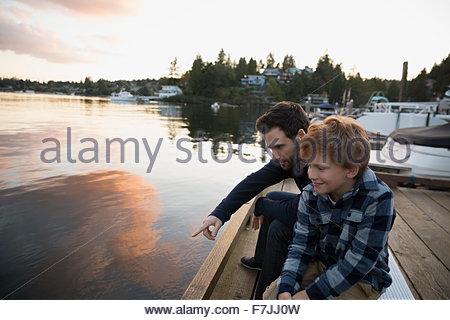Père et fils, sur le lac au coucher du soleil dock Banque D'Images