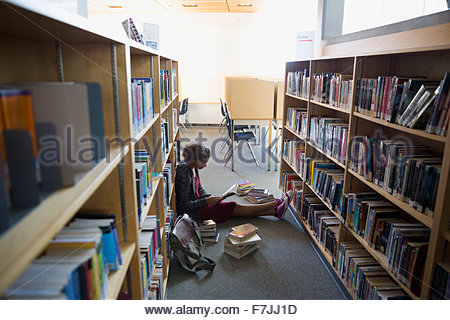 High school student studying on library floor Banque D'Images