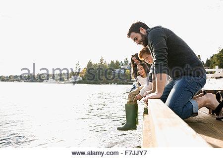 Famille penché sur le lac de garde-corps dock Banque D'Images