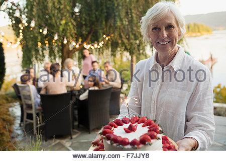 Portrait of smiling senior woman serving strawberry cake patio Banque D'Images