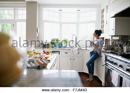 Pensive woman drinking coffee looking out window cuisine Banque D'Images