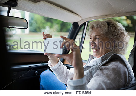 Senior woman using camera phone in car Banque D'Images