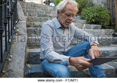 Senior man using digital tablet sur les marches de pierre Banque D'Images