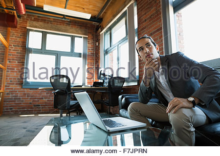 Pensive businessman au bureau de l'ordinateur portable sur canapé Banque D'Images