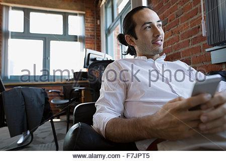 Pensive businessman with cell phone sur canapé bureau Banque D'Images