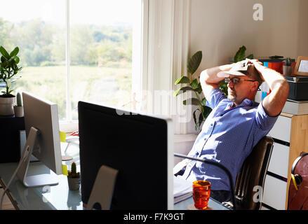 L'homme en se penchant en arrière de travail sunny home office Banque D'Images
