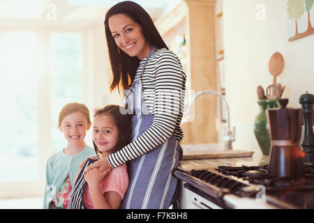 Portrait smiling mother and daughters in kitchen Banque D'Images