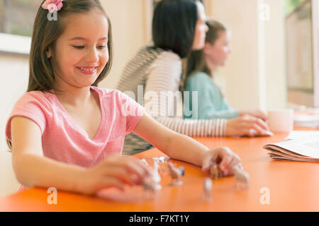 Smiling girl Playing with miniature animaux Banque D'Images