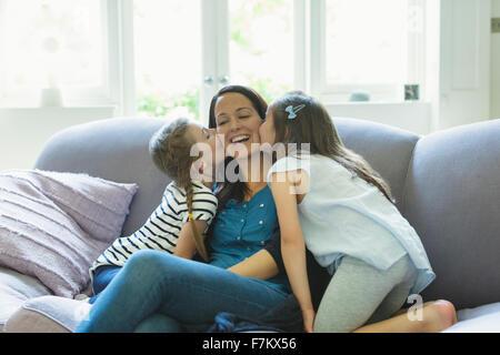 Filles embrassant les joues de la mère sur le sofa du salon Banque D'Images