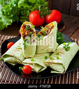 Burritos wraps avec la viande hachée et de légumes sur un fond de bois Banque D'Images