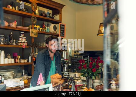 Commerçant derrière comptoir à café Banque D'Images