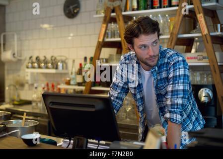 Propriétaire de café debout derrière la caisse enregistreuse Banque D'Images