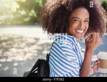 Portrait femme enthousiaste avec afro drinking coffee in park Banque D'Images