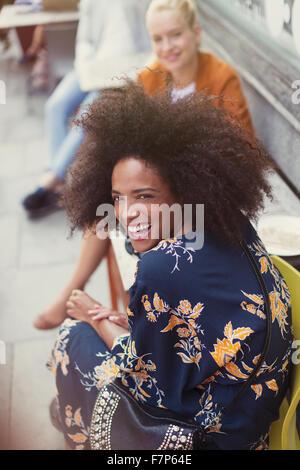 Portrait femme enthousiaste avec afro at sidewalk cafe Banque D'Images