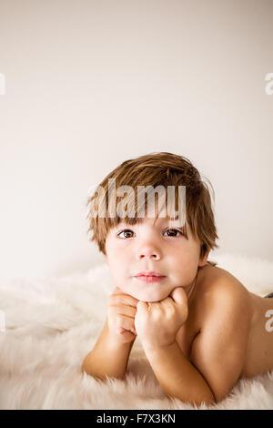 Portrait d'un garçon allongé sur un tapis appuyé sur ses coudes Banque D'Images
