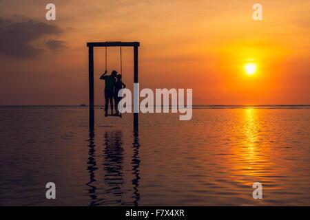 Silhouette of man and woman kissing, debout sur une balançoire dans la mer au coucher du soleil, de l'Indonésie Banque D'Images