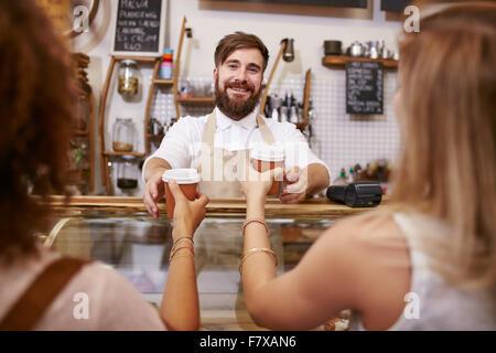 Jeune homme avec barbe, debout derrière le comptoir et café servant du café pour deux femmes. Young man working Banque D'Images
