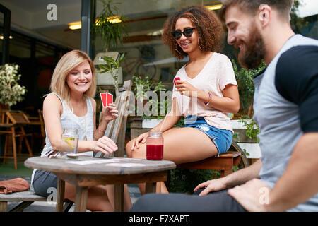 Groupe d'amis jouer à un jeu de cartes dans un café. Woman picking up un jeu de carte sur table et de sourire. Banque D'Images
