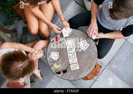 Vue du haut de trois jeunes jouant aux cartes at sidewalk cafe. Les jeunes gens assis autour d'une table basse et Banque D'Images