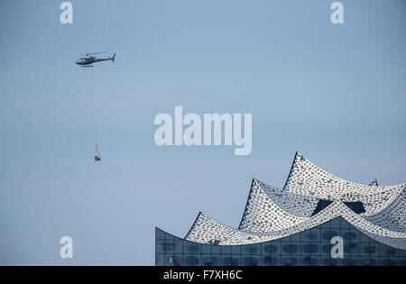 Un hélicoptère transporte les matériaux de construction du toit de l'Elbphilharmonie (Elbe Philharmonic Concert Banque D'Images