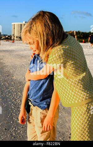 Jeune pré-adolescent de son jeune frère soeur donnant une accolade sur Siesta Key Beach en Floride Banque D'Images