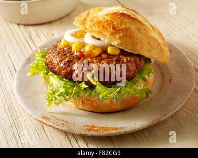 Près d'un burger de boeuf, dans un hambuger rouleau croustillant blanc avec relish de maïs et l'oignon et de laitue Banque D'Images