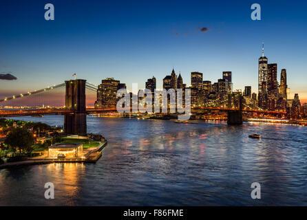 Pont de Brooklyn et Manhattan illuminée au crépuscule. Quartier des gratte-ciel de refléter dans l'East River, New York.