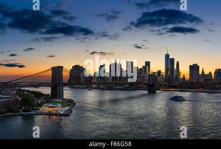 Portrait du pont de Brooklyn, East River, Lower Manhattan, des gratte-ciel et nuages au coucher du soleil. New York City