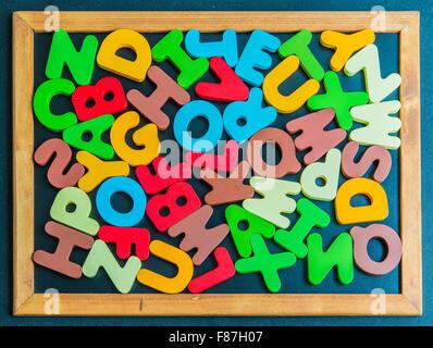 Mélanger en bois coloré Alphabet mot sur tableau noir Banque D'Images