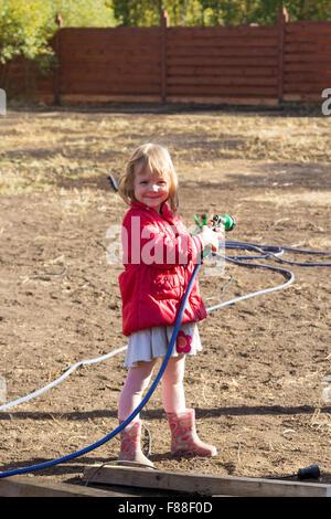 Petite fille debout avec arrosage dans ses mains Banque D'Images