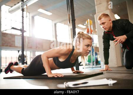 Tourné à l'intérieur de jeunes femmes l'exercice avec un entraîneur personnel à la salle de sport. Femme Fitness Banque D'Images