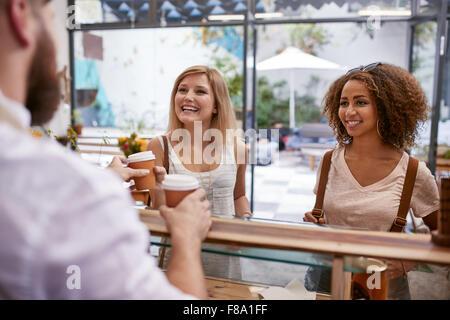 Tourné à l'intérieur de deux jeunes femmes amis sourire alors qu'ils reçoivent leurs boissons chaudes au café comptoir. Banque D'Images