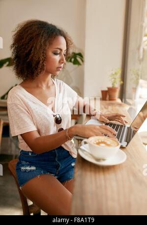Tourné à l'intérieur de la jeune femme assise dans un café à l'aide d'ordinateur portable. African girl surf internet Banque D'Images