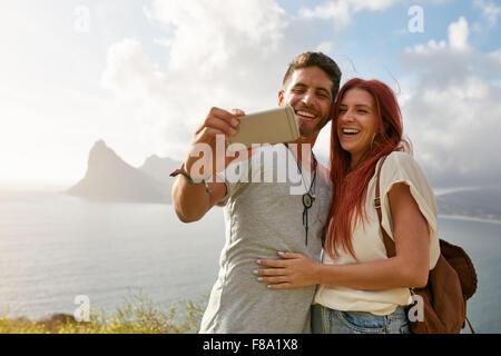 Smiling young friends taking self portrait extérieur en été. Jeune homme avec sa petite amie en tenant avec mobile Banque D'Images