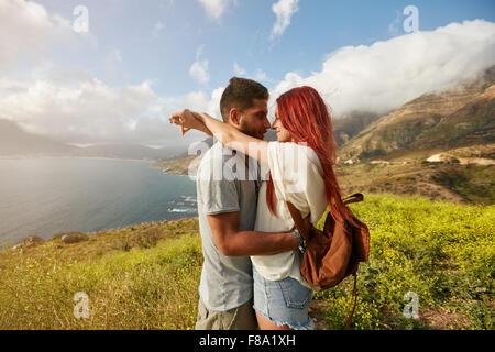 Vue latérale du couple en vacances. L'homme et la femme enlacés à l'extérieur. Banque D'Images