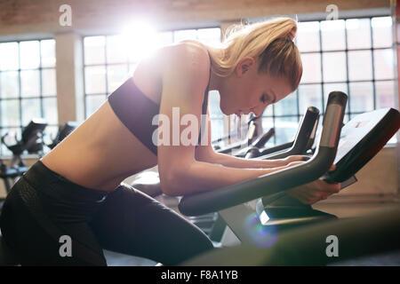 Woman taking casser pendant l'entraînement en vélo sport. Femme à vélo fitness cardio faire l'exercice. Banque D'Images