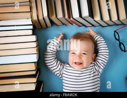 Un an bébé avec spectackles et livres Banque D'Images