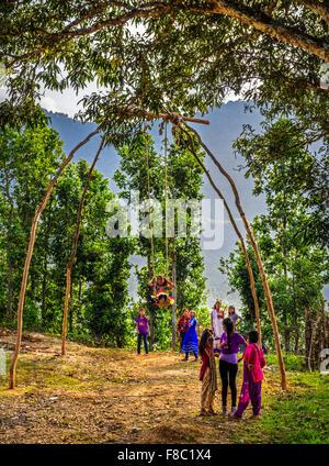Enfants népalais jouant sur une balançoire bambou traditionnel appelé linge ping Banque D'Images