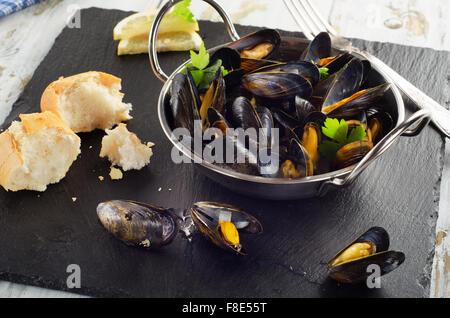 Les moules cuites dans un plat de cuisson sur fond sombre. Selective focus