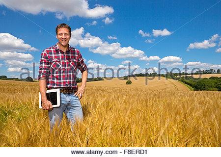 Portrait smiling farmer with digital tablet in rural crop field orge ensoleillée en été Banque D'Images