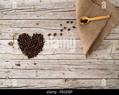 Forme de coeur fait de grains de café et cuillère en bois sur fond de bois Banque D'Images