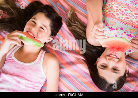 Caucasian twin sisters eating watermelon Banque D'Images