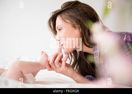 Mother kissing feet of baby girl Banque D'Images