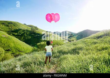 Black Girl with balloons on rural hillside Banque D'Images