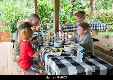 Caucasian family eating at picnic table outdoors Banque D'Images