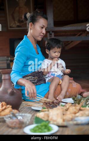 Asian mother and son eating sur tapis tissé Banque D'Images